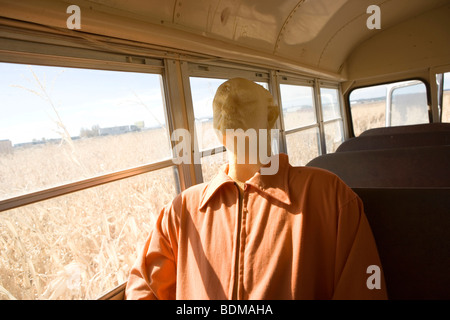 mannequin dressed in prisoner's clothing, riding in a school bus, abandoned field, corn, farm, creepy, halloween - Stock Photo