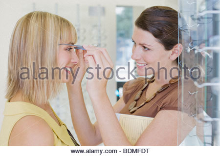 Woman trying on glasses in optometrist's shop - Stock Photo