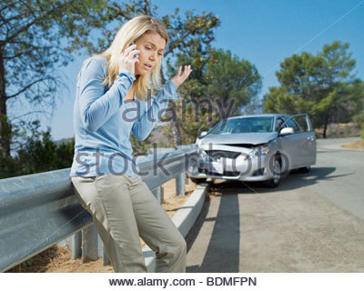 Frustrated woman using cell phone next to car wrecked on guardrail - Stock Photo