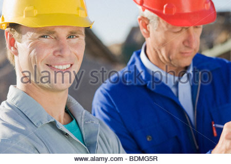 Construction workers in coveralls and hard-hats - Stock Photo