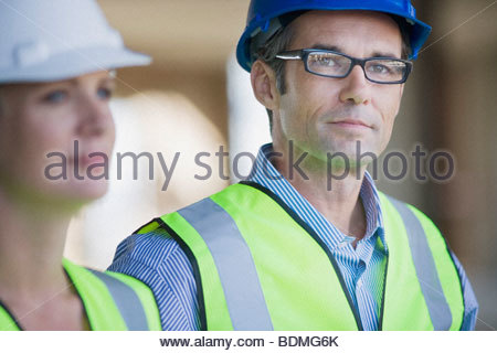 Co-workers in hard-hats and safety vests - Stock Photo