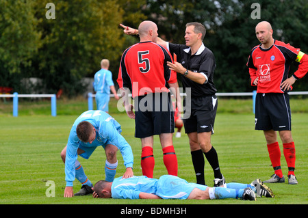 referee sends player off during football match - Stock Photo