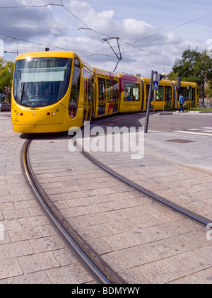 Yellow Orange City Tram taking a curve, Mulhouse France - Stock Photo