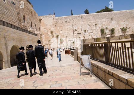 Hasidic Jewish young men wearing bekishe, long satin coats, walk toward the Western Wall for Sabbath prayers. - Stock Photo