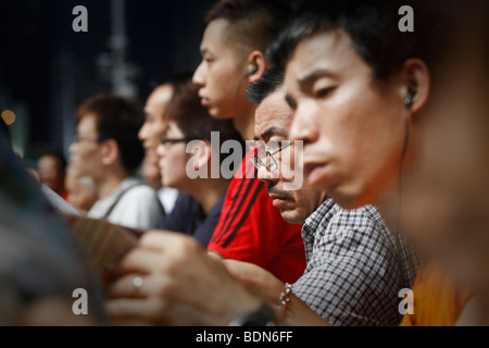 Punters study the race form at a night horse racing event at the Happy Valley race course in Hong Kong. - Stock Photo