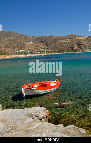 Children are snorkling near the fishing boat pier in the Mylopotas beach, one of the best beaches to be found anywhere - Stock Photo