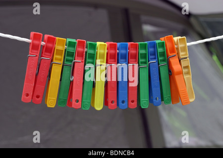 Clothes pegs hanging on a line outside a family tent - Stock Photo