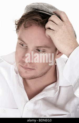 Portrait of a young, pensive man, wearing a white shirt and a hat, scratching his head - Stock Photo