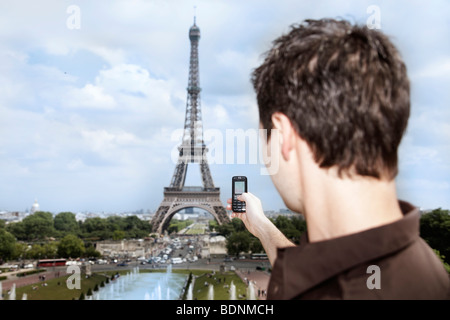 Young man in front of the Eiffel Tower, Paris, France, Europe - Stock Photo