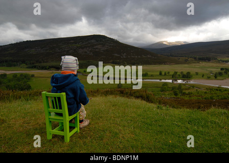 Young girl sitting on a green chair, looking at the Scottish Highlands, river and forests, Scotland, Europe - Stock Photo