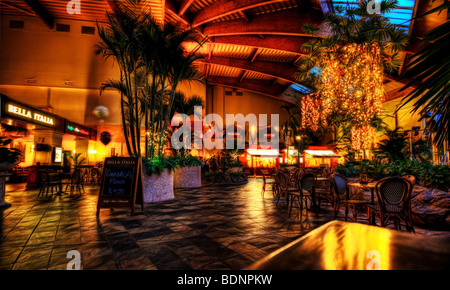 Evening eatery romantically lit with the lighting reflected in a checkered tiled floor - Stock Photo