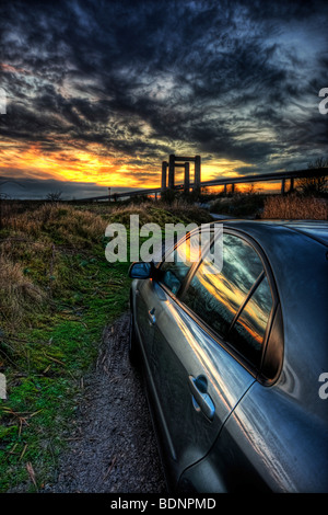 Evening sunset over the river swale reflected in the side of a shiny car with the new and old swale bridges on the - Stock Photo