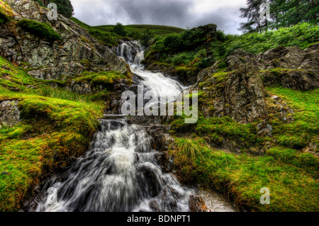 The majestic power of a long exposure shot of a waterfall in the lake district with water crashing over the rocks - Stock Photo
