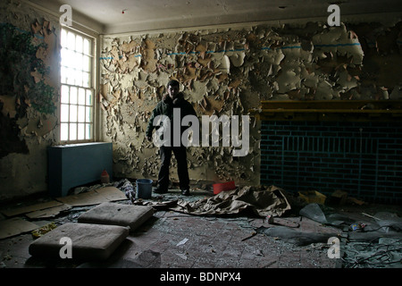 A man standing in a derelict room - Stock Photo