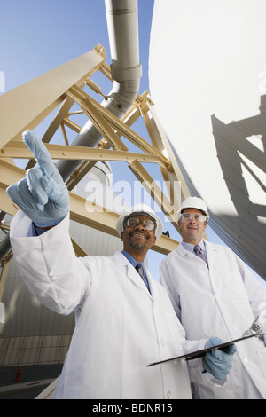 Scientist pointing forward with another scientist standing beside him - Stock Photo