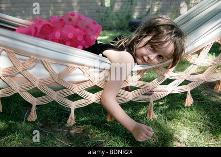 Portrait of young girl lying in hammock - Stock Photo
