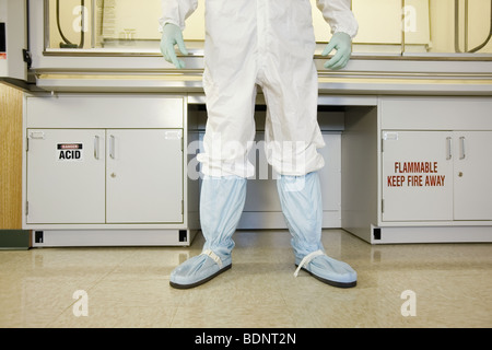 Scientist in protective wear standing in a clean room - Stock Photo