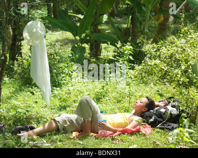 Young woman lying in tropical forest, sunbathing - Stock Photo