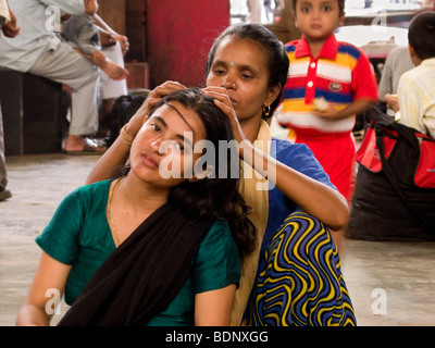 A woman checking the head of a girl at Mumbai Central station. Mumbai. India. - Stock Photo