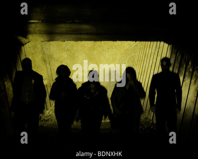 Silhouetted figures walking into a tunnel - Stock Photo