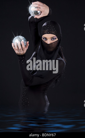 party dancer in ninja dress with disco balls - Stock Photo
