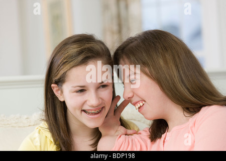Teenage girl whispering to her sister - Stock Photo