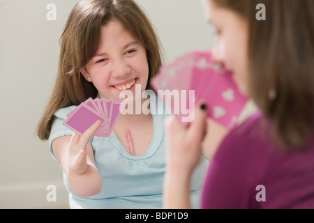 Two teenage girls playing cards - Stock Photo