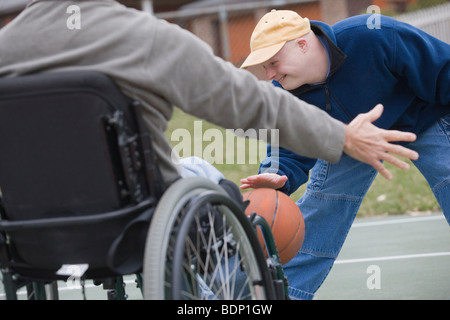 Disabled man playing basketball with his son - Stock Photo