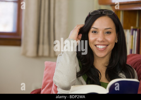 Portrait of a Hispanic woman holding a book and smiling - Stock Photo