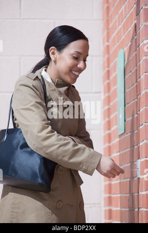 Hispanic woman inserting a bank card into the bank access slot - Stock Photo