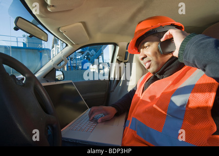 Engineer working on a laptop and talking on a mobile phone in a car - Stock Photo