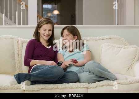 Two teenage girls sitting on a couch and using mobile phones - Stock Photo