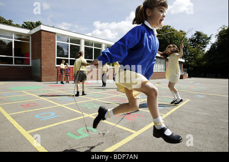 Schoolgirls skipping in a primary school playground in the UK. - Stock Photo