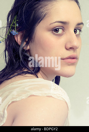 A young girl with dark wet hair looking at the camera - Stock Photo