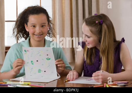 Girl sitting with her friend and showing a drawing - Stock Photo