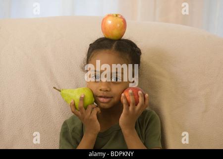 Portrait of a Hispanic girl holding fruits - Stock Photo