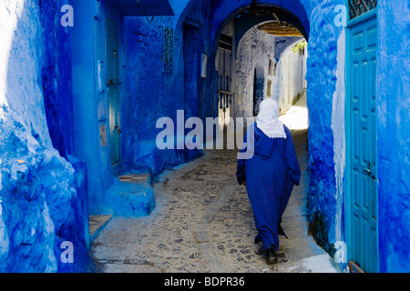 Chefchaouen, woman in blue jalaba and traditional blue-painted doors and walls in the old town. - Stock Photo