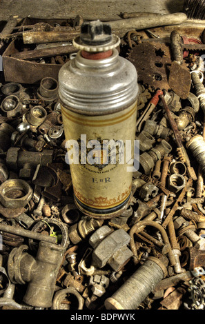 An old thermos flask in a box of old nuts and bolts - Stock Photo