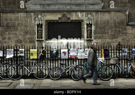 A middle aged man walking along a street in Cambridge, England past a line of bicycles - Stock Photo