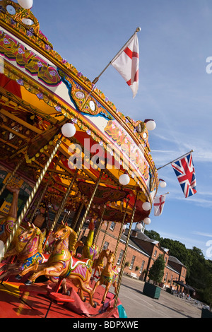 UK, England, Cheshire, Knutsford, Tatton Hall, traditional steam powered merry go round in the stable block courtyard - Stock Photo