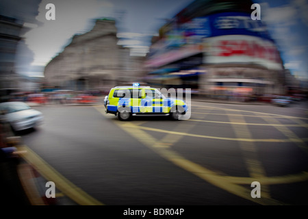 Police car speeding through Piccadilly Circus in London - Stock Photo