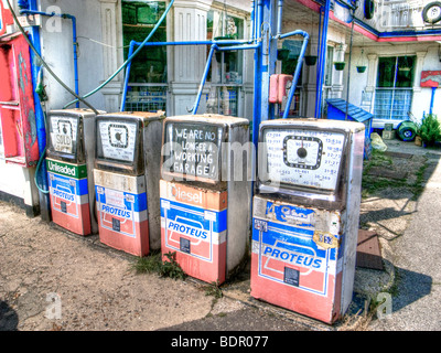 Old petrol pumps in a garage forecourt - Stock Photo