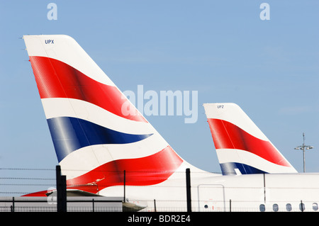 British Airways Airbus A319 tailfins, Terminal 5, London Heathrow Airport, with security fence in foreground. - Stock Photo