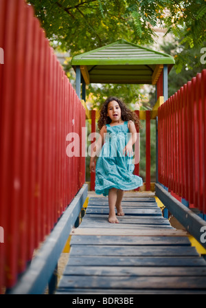 girl runing on a wooden 'bridge' in a playground - Stock Photo