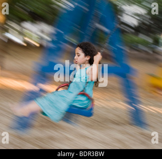 girl in blue dress on a swing with motion blur - Stock Photo