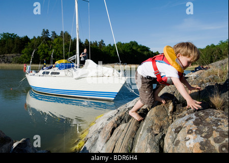 A boy climbing on a cliff Sweden. - Stock Photo