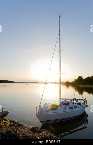 A sailing-boat in sunset Sweden. - Stock Photo