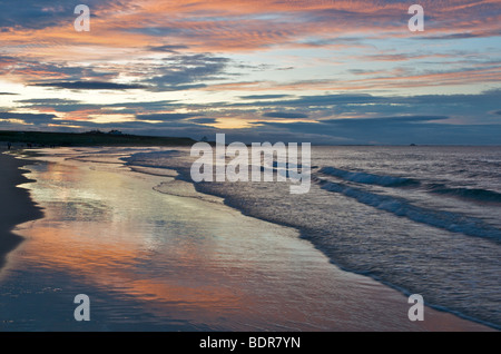 Dusk on the Northumberland coast at Bamburgh beach. Lindisfarne Castle in the distance. - Stock Photo