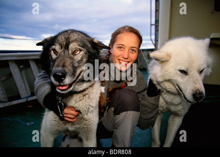 A woman and two dogs on a boat, Svalbard. - Stock Photo