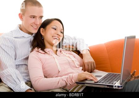 Junges Paar sitzt lachend mit einem Laptop auf dem Sofa und surft im Internet - Stock Photo